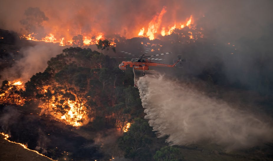 A firefighting helicopter tackles a bushfire near Bairnsdale in Victoria's East Gippsland region, Australia