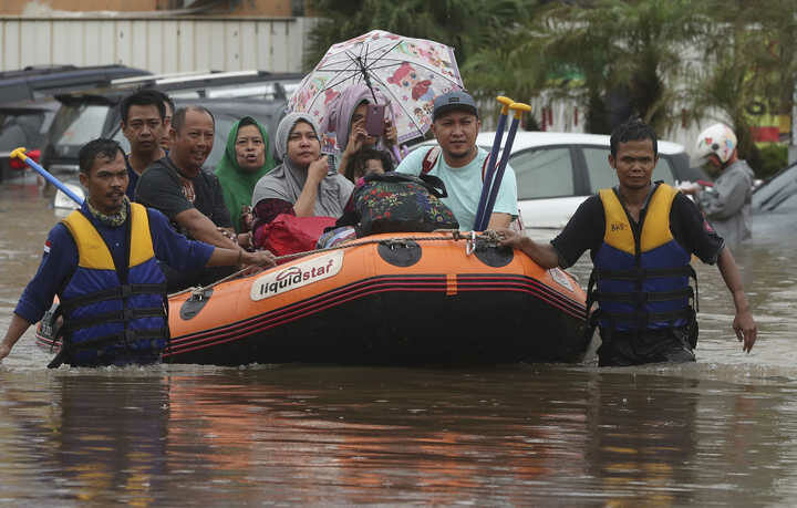 Indonesia rescue team evacuate residents from their flooded house at Jatibening on the outskirt of Jakarta, Indonesia, Wednesday, Jan. 1, 2020.